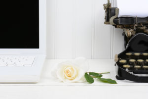 Closeup of a white desk with a rose laying between a modern laptop computer and an antique typewriter. Only half of the laptop and typewriter are shown. Horizontal format.
